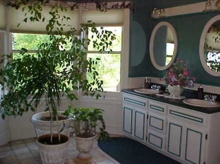 Have you ever seen a bathroom with a bay window?  Now you have!  The treetops outside the window are beautiful and comforting.  Just to the left of the picture is the claw foot tub replica.  This bathroom even includes the laundry space.