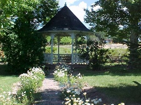 What Victorian home would be complete without the white gazebo at the end of the flowered path?  Just beyond is the hay field that is irrigated and ready for some pampered horses!  They even have a pond in addition to the pole barn.
